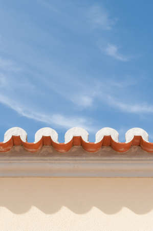 External wall of villa with roof eaves  clay pantiles against sunny sky Stock Photo