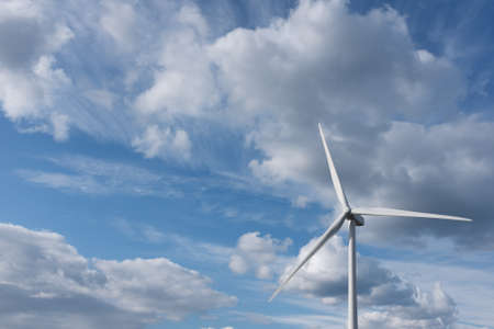 Wind turbine photographed against dramatic cloudy blue sky