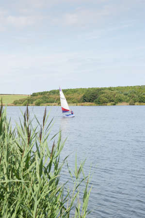 Editorial Sailing Dinghy on lake at Druridge Bay Country Park Northumberland UK. Taken 8 August 2010