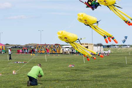 expositor: Blyth Northumberland Reino Unido: 04 de mayo de 2015. Expositor ajusta cuerdas tensoras de kite en Blyth Kite Festival 2015