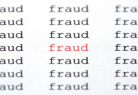 The word fraud in color red on white paper surrounded by similar text in black type