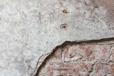 Brick wall with plaster partially removed. Suitable as background Stock Photo