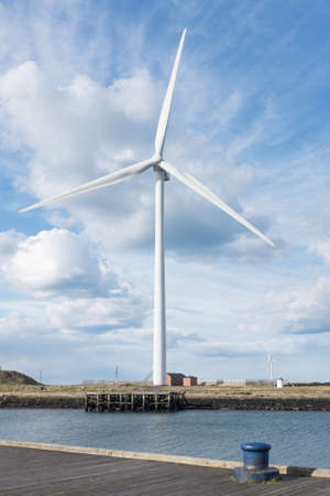 Wind turbine photographed against dramatic cloudy blue sky on bank of river Blyth Northumberland UK Editorial