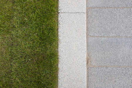 Grey stone paving  kerb adjacent to green grass lawn