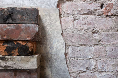 Stack of bricks next to partially removed wall plaster suitable as background Stock Photo