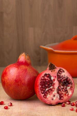 punica granatum: Whole  and cut Pomegranate on wood chopping board Punica granatum