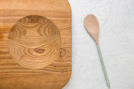 Decorated wooden spoon and chopping board on white