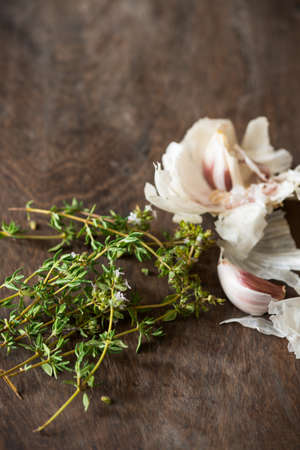 Garlic  Thyme food ingredients resting on wooden chopping board