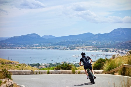 Downhill e-bike in Majorca with scenic mountains and Mediterran Sea in the background 免版税图像