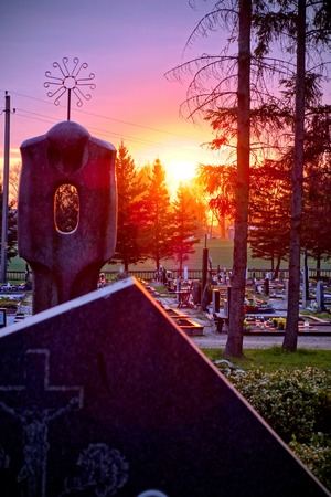 tombstones and silhouettes of crosses and trees against sky at sunset in an old Christian cemetery