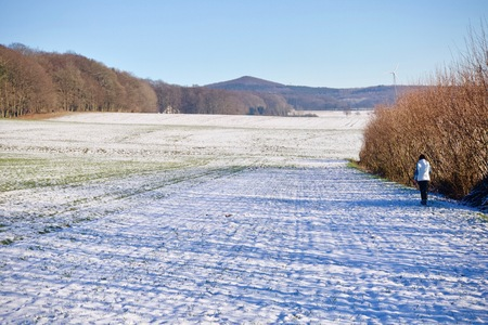 Person walking away down a snowy winter path through a field in a scenic landscape conceptual of the seasons 스톡 콘텐츠