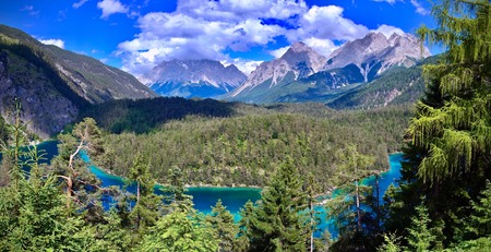 Zugspitze, alpine peaks and valley under a blue cloudy sky with a cyan lake in the foreground in Biberwier, Tirol