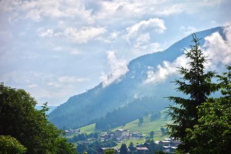 Peaceful scenic landscape of a village with lush green alpine peak under a blue cloudy sky in Saalbach, Austria