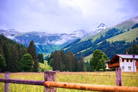 scenic landscape of green alpine mountain with a snowy peak under a foggy sky with a wood fence and chalets on the foreground at Talschluss in Saalbach, Austria