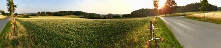 panorama of country field at sunset with a speed bike on a country road