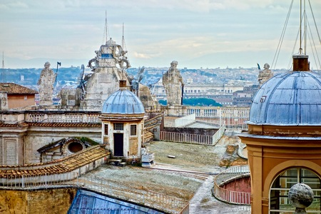 on the roof of the peters dome, Vatican, Rome, Italy with sculpture and cloudy skay in the background Publikacyjne