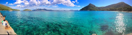 Panorama of a crystal clear blue tropical ocean with people sitting on a pier and distant mountains with a moored luxury boat conceptual of summer vacations