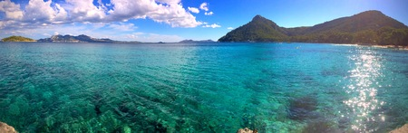 Panorama of a crystal clear blue tropical ocean and distant mountains conceptual of summer vacations