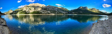 Panorama of a water reservoir at Gorg Blau with rocks outdoors in a mountain valley Reklamní fotografie