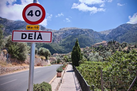view of Deia with a road and speed limit sign Stok Fotoğraf