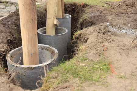 Concrete tube serving as fundament for wood column.