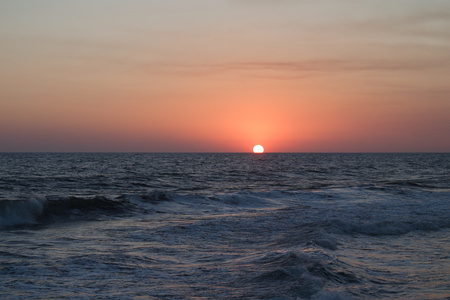 Orange sun halfway disappeared into the ocean.