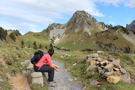 Hiker (woman 20-25) sitting on rock next to pathway with scenic mountain view. Stockfoto