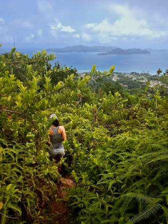 Female hiker in green jungle with praslin island (Seychelles) in the background.