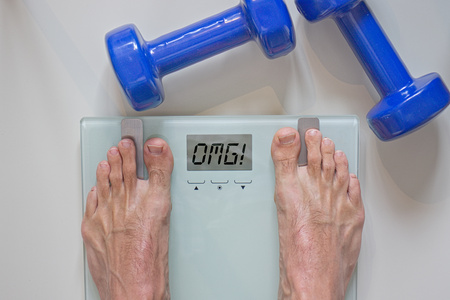 Man standing on scale. View of feet, lifting weights and text omg written on scale.
