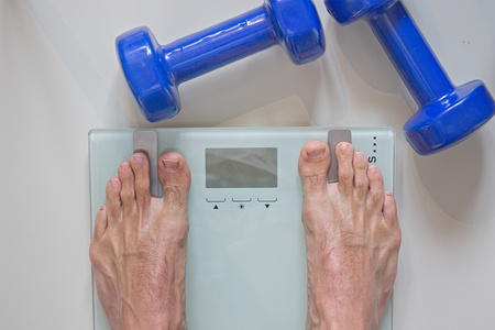 Man standing on scale. View of feet, lifting weights and blank scale. Stock Photo