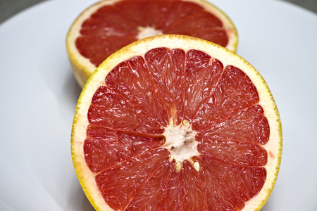 Two pink grapefruit halves on white plate.