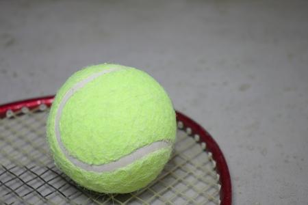 Tennis ball on racket on grey surface. 写真素材