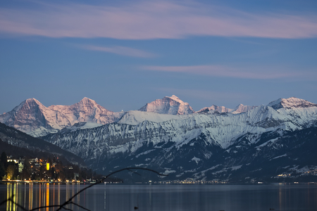 Famous mountain range Eiger, Moench and Jungfrau with snow on peaks at sunset reflecting in lake Thun..