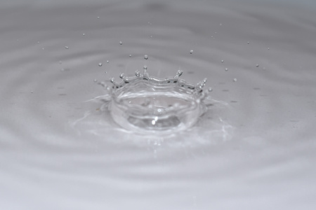 Water droplet creating splash and ripple on white surface.