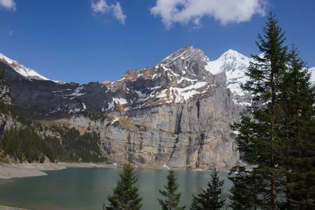 View of Lake Oeschinen (Oeschinensee) through trees with turquoise water and mountain range (Bluemlisalp) in Kandersteg. 写真素材