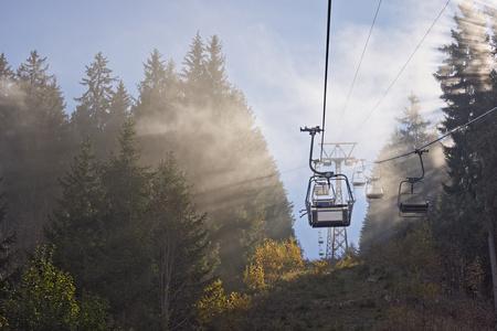 Ski sitting lift leading through autumn fog. 写真素材