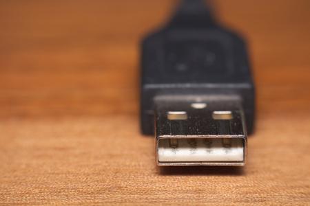 Single usb plug macro on wooden surface.