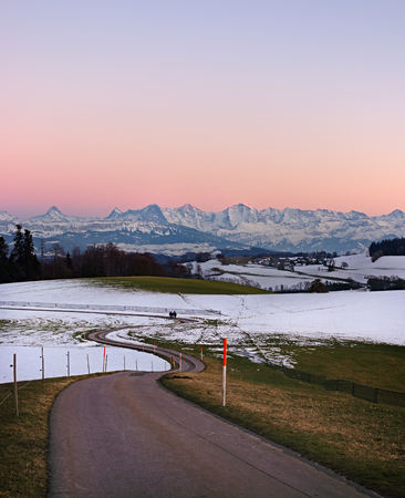 Pathway leading through winter hills on Gurten mountain with colorful evening sky and famous jungfrau mountain range (Eiger, Moench and Jungfrau).