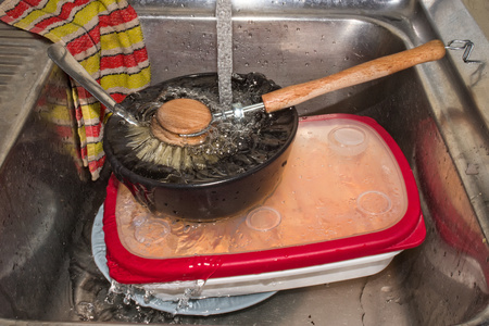 Water running over dirty dishes in metal sink with flannel.