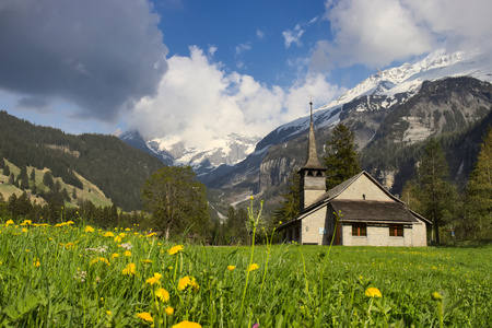 Church in field of dandelions with alps in the background.
