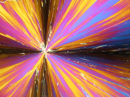 Liquid crystal in its crystal state under polarized light microscope forming a flower like texture. Abstract orange flower like background.