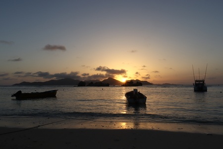 Tropical sunset at beach. Anchored boats in the ocean and the Island of Praslin. 写真素材