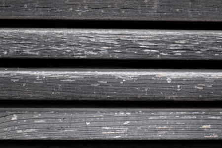 Close up of texture of grey weathered wood planks with gaps.