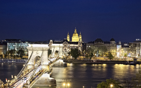 Chain Bridge leading to Pest side with Basilika in the distance in Budapest, Hungary. Landmarks illuminated by city lights at night.
