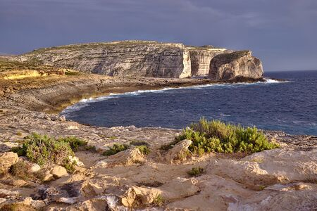 Beautiful round bay, green plants and fungus rock cliffs at sunset in gozo. Orange sunset light with grey storm clouds.