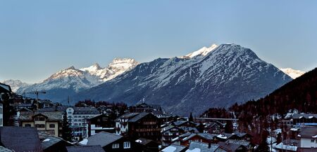 Traditional wooden Hotels and Huts in Saas-Fee Ski Resort with morning light on mountain range in Switzerland