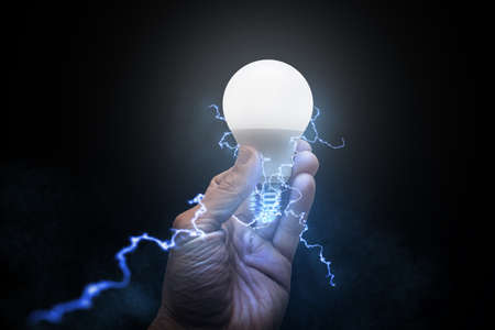 Man holding glowing light bulb with electricity and lightning bolts against black brackground. Concept of electricity or creative idea.
