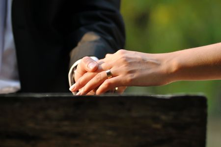 Groom holding his bride hand with a ring photo