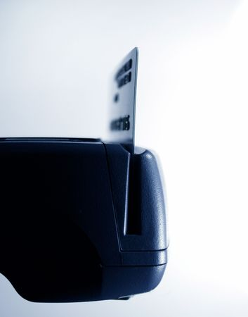 Lateral view of a POS credit card reader processing a credit card. Studio shot. Narrow focus on some of the keys photo