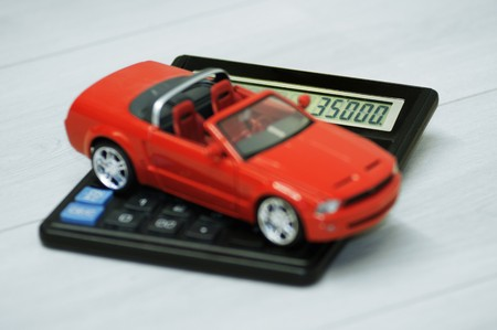 Red car over a calculator wich shows price of the car.